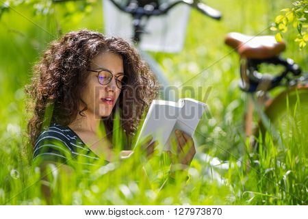 Lovely brunette teen with bicycle reading a book in a park on a sunny day