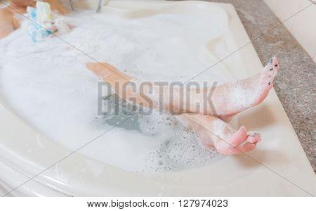 Beautiful girl showering and washing legs in bathtub.