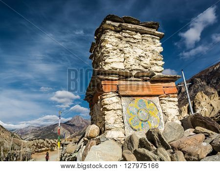 Buddhist drawing on a stone structure on trekking path. Annapurna region, Nepal.