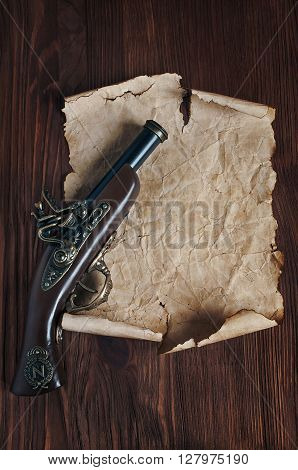 Retro pistol or musket and parchment on a wooden table
