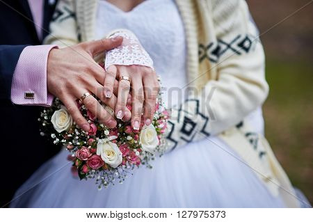 hands of the bride and groom with rings on a beautiful wedding bouquet.
