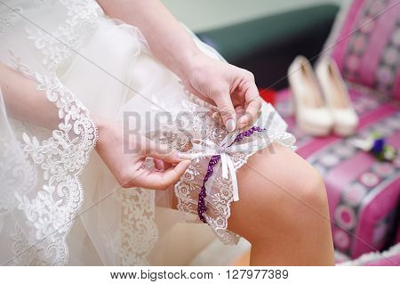bride dresses garter on the leg. Picture of beautiful female barefoot legs in wedding dress.