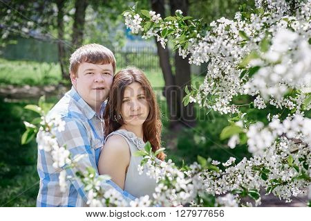 Young couple posing in blossoming spring garden.