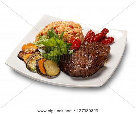 Risotto with fillet mignon steak. White background.