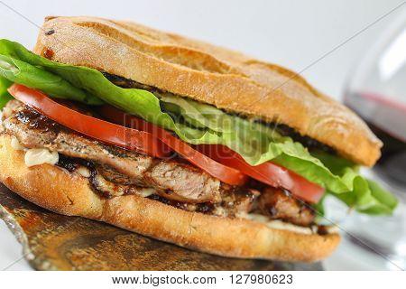 Tasty Pork Steak Sandwich In A Ciabatta With Tomatos, Lettuce