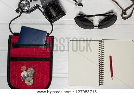 Travel items on wooden rustic table overhead view