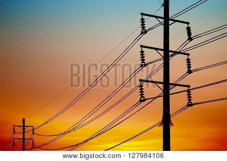 High voltage electricity post junction with orange sky background