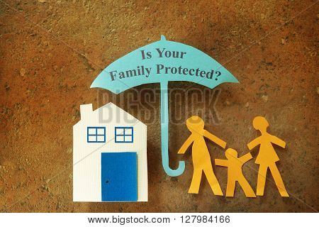 Paper cutout family with house under an umbrella with family protection text
