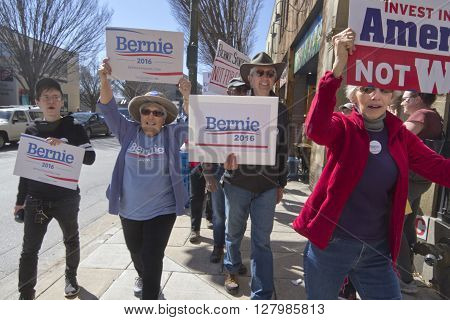 Asheville North Carolina USA - February 28 2016: Enthusiastic supporters of Bernie Sanders for president march cthrough the streets carrying signs on February 28 2016 in downtown Asheville NC