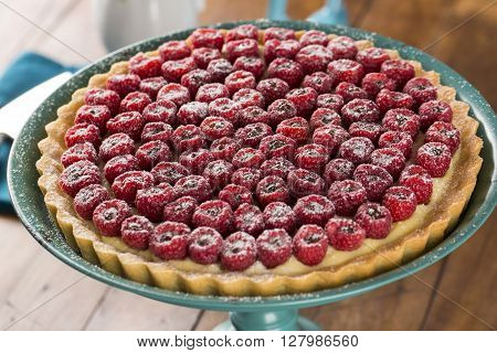 A Delicious Raspberry Pie With Chocolate Served On A Green Plate Over The Table.