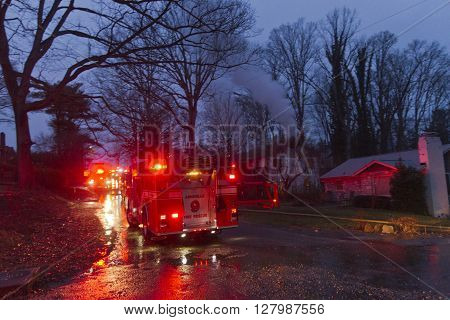 Asheville, North Carolina, USA - February 16, 2016: A firetruck lights up the night parked on a street next to a house on fire with smoke coming out of it