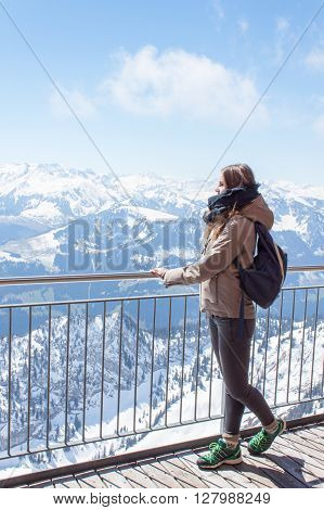 Beautiful brown-haired girl on the terrace of a chalet in the high mountains. A young girl and a summer day in the mountains. Swiss Alps in summer sunny day.