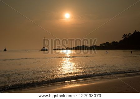 Catamaran and people in the sea at sunset