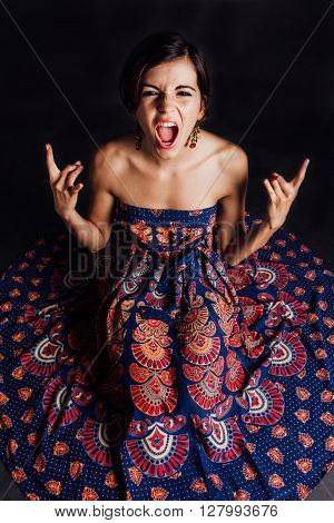 Rocker woman yelling and showing rock sign - isolated on black.