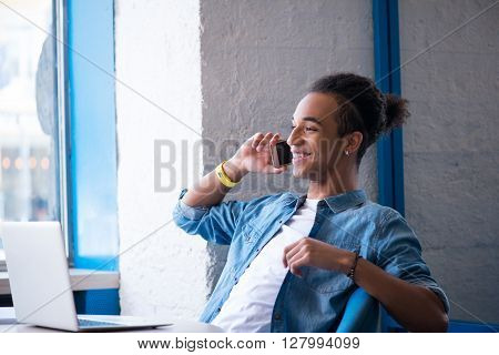 Glad to hear you. Cheerful content pleasant guy sitting at the table and talking on mobile phone while