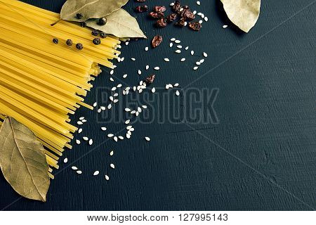 Raw spaghetti and Bay leaf, barberry, pepper, sesame seeds on black-blue wooden background, top view place for text ** Note: Shallow depth of field