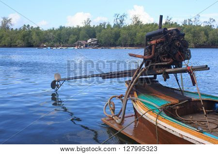 long tail boat motor engine in tranquil sea in fisherman village Trang Thailand