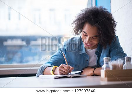 Inspiration in mind. Cheerful positive delighted guy sitting at the table and resting in the cafe while making notes