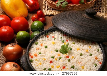 Appetizing healthy rice with vegetables in white plate on a wooden background. rice colored