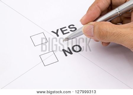 Man hand with pen over document select Yes or No.