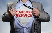 Businessman in classic superhero pose tearing his shirt open to reveal t shirt with customer service poster
