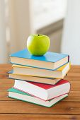 education, school, literature, reading and knowledge concept - close up of books and green apple on  poster