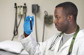 image of phlebotomy  - A black man African American doctor holding a test tube vial sample of blood - JPG
