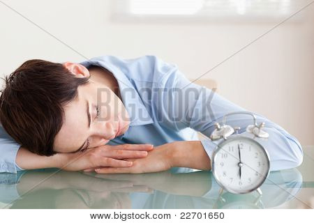 Sleeping Businesswoman With Her Head On The Desk Next To An Alar