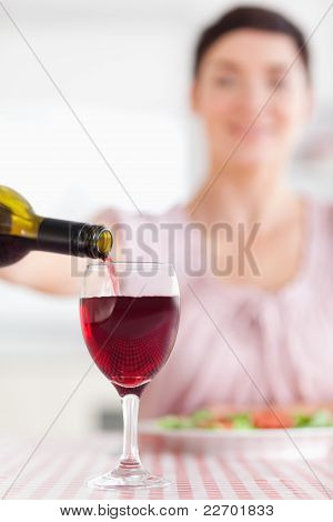 Brunette Woman Pouring Redwine In A Glass
