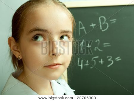 Schoolgirl Thinking About Exercises Written On The Blackboard