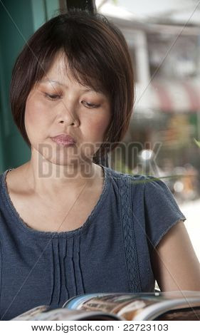 Asian Woman Reading A Magazine