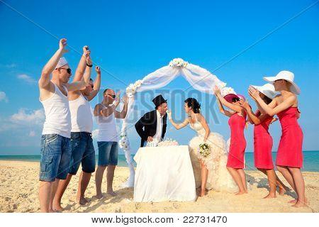Novia y novio bajo el arco en la playa tratando de tomar un bocado de pastel de boda.