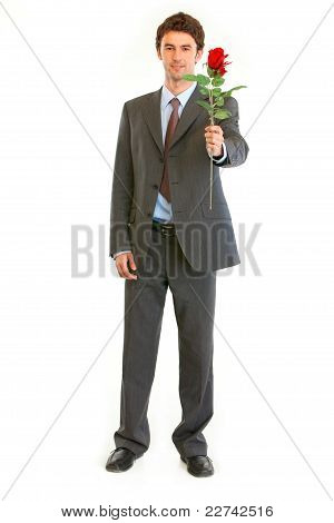Full Length Portrait Of Smiling Modern Businessman With Red Rose In Hand