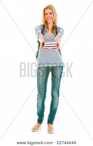 Full Length Portrait Of Smiling Teen Girl With Schoolbag Giving Books