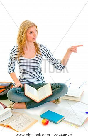 Cheerful Teen Girl Sitting On Floor Among Schoolbooks And Pointing In Corner