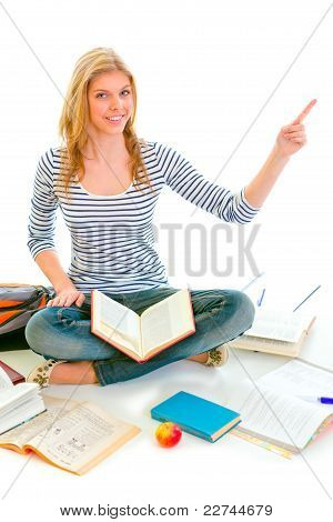 Smiling Teen Girl Sitting On Floor Among Schoolbooks And Pointing In Corner