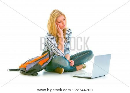 Tired Teen Girl Sitting On Floor With Backpack And Looking On Laptop