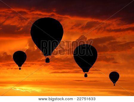 Silhuetas de quatro balões de ar quente no nascer do sol