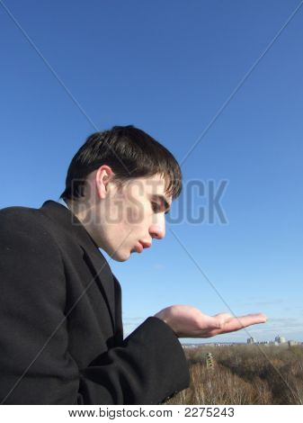 Businessman Blowing On Hand