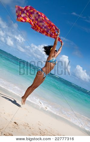 gegerbte jungen europäischen Frauen mit rot und orange Pareo direkt am weißen Sandstrand