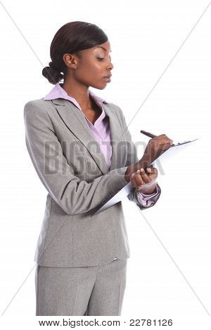 Serious Black Business Woman Writing On Clipboard