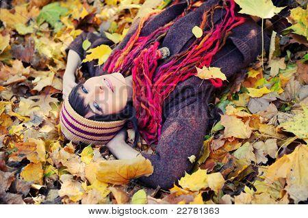 Happy brunette girl lying in autumn leaves. Outdoor.