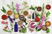Natural herbal medicine selection with herbs and flowers in wooden bowls and loose, glass aromathera poster