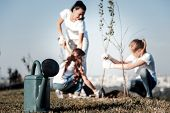 Watering Plants. Selective Focus Of A Watering Pot Standing On The Ground With Positive Nice People  poster