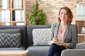 Attractive female psychologist sitting in armchair at office poster