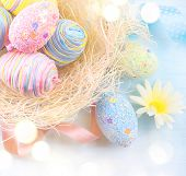 Easter colorful eggs background. Beautiful colorful eggs with decorations over blue wooden backgroun poster