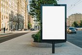 Vertical Blank Glowing Billboard On The City Street. In The Background Buildings And Road With Cars. poster