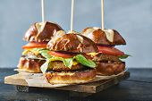 three vegan burger sliders with pretzel buns poster