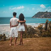 Romantic young couple on a tropical island paradise standing arm in arm looking out over a tranquil  poster