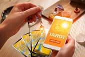 Tarot cards dowsing tool in hand and smartphone with modern fortunetelling application on screen as  poster